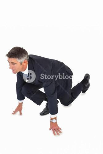 Businessman with hands and one knee on the floor