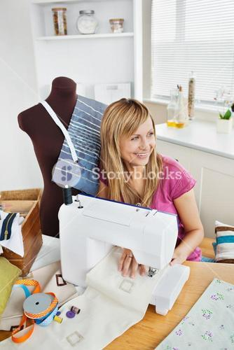 Delighted woman sewing clothes in the kitchen