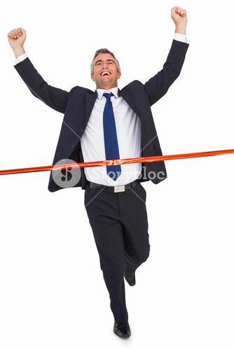 Businessman crossing finish line and cheering