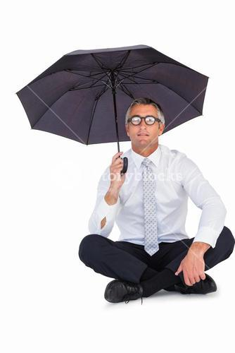 Businessman wearing glasses sheltering with umbrella