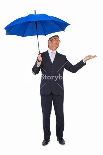 Businessman under umbrella with hand out