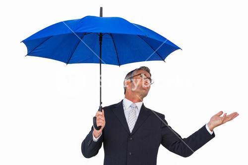 Businessman under blue umbrella with hand out