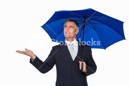 Smiling businessman under umbrella with hand out