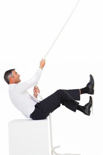 Businessman sitting and pulling a rope