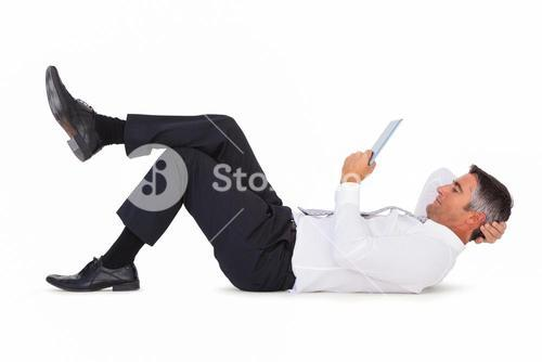 Peaceful businessman lying and using tablet pc
