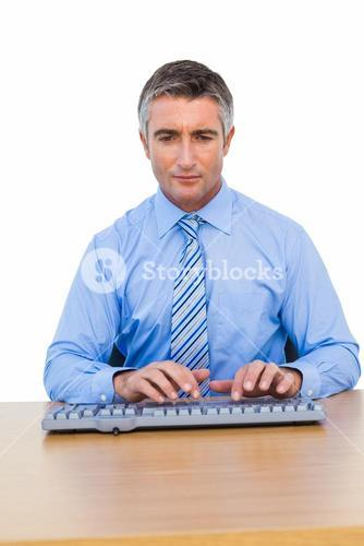 Focused businessman typing on keyboard