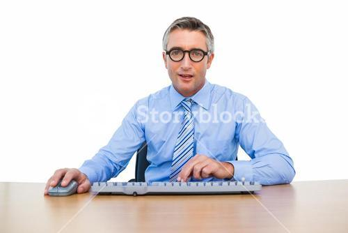 Smiling businessman using computing mouse and keyboard