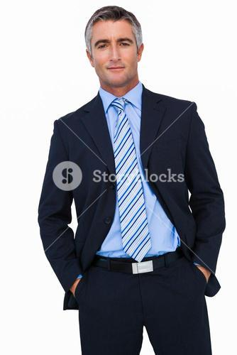 Smiling businessman in suit with hands in pocket posing