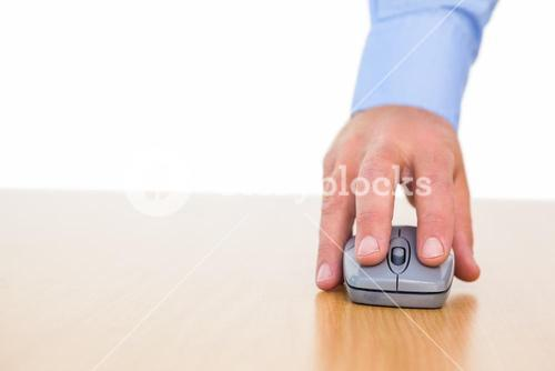 Hand of a businessman using mouse at desk