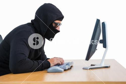 Burglar with sunglasses typing on keyboard