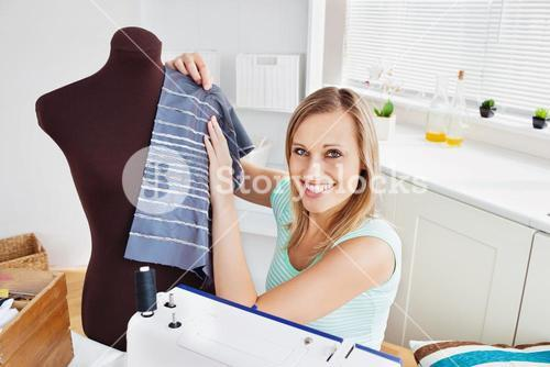 Merry woman sewing clothes at home