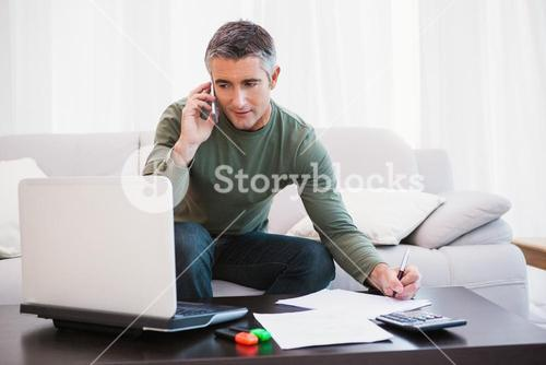 Man with laptop phoning and taking notes