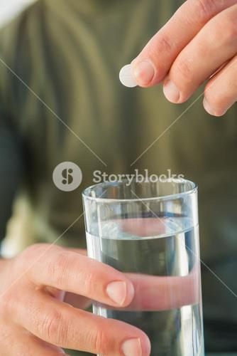 Close up of a man holding glass of water and pill