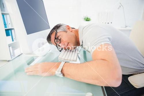 Man with glasses sleeping on the keyboard