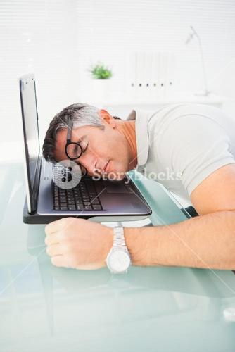 Man with glasses sleeping on his laptop