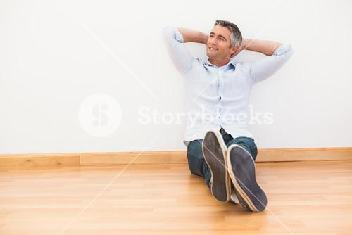 Smiling man sitting on the parquet relaxing
