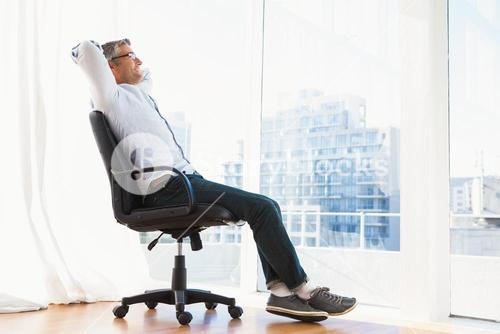 Smiling man with glasses sitting on office chair and relaxing