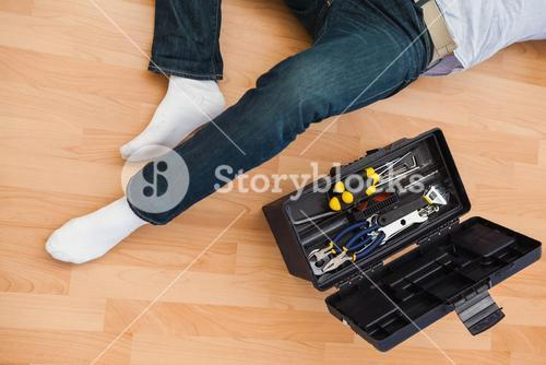 Mid section of a man lying with tools box