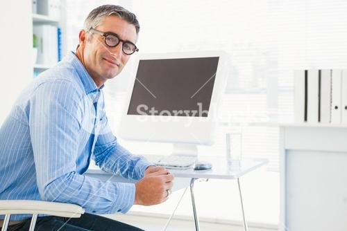 Smiling man with glasses at his desk looking at camera