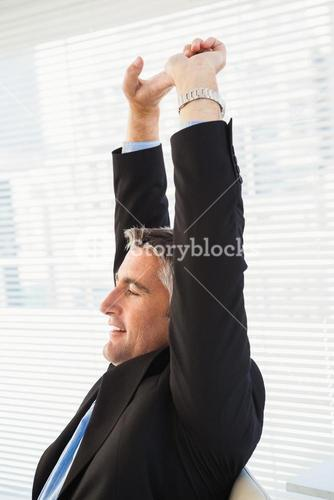 Peaceful businessman stretching his arms