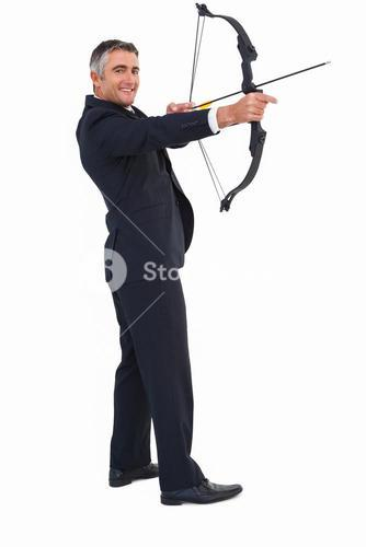 Smiling businessman drawing a bow