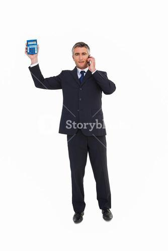 Businessman on the phone showing a calculator