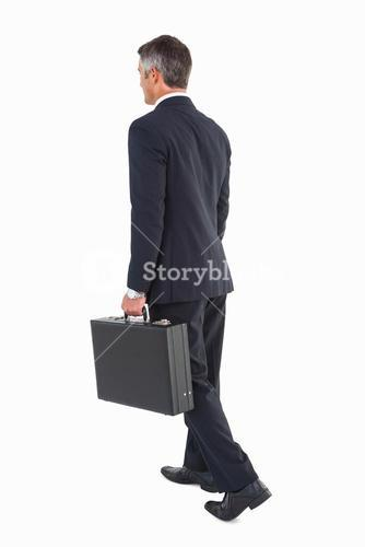 Businessman walking and holding briefcase