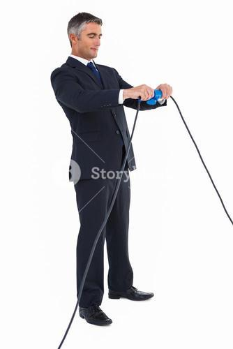 Smiling businessman connecting cables together