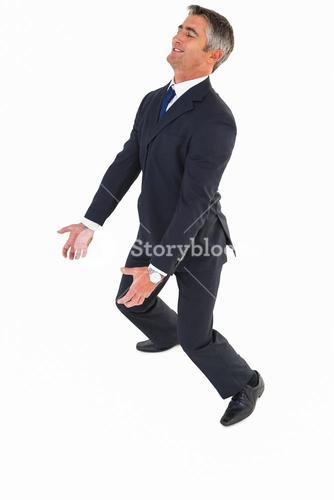 Happy businessman in suit carrying
