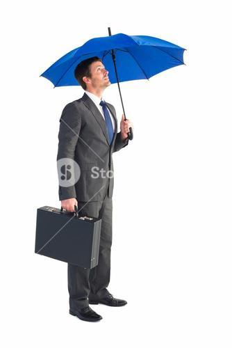 Businessman sheltering under blue umbrella