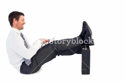 Businessman with feet up on briefcase