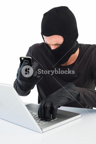 Hacker using laptop and phone