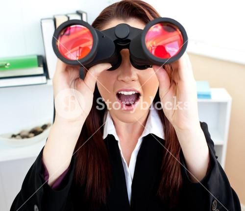 Surprised businesswoman sitting on a chair and looking through binoculars