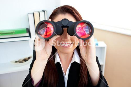 Radiant businesswoman sitting on a chair and looking through binoculars