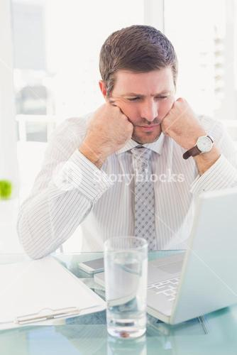 A businessman looking at laptop at desk