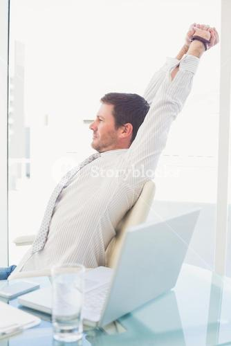 A businessman stretching in swivel chair
