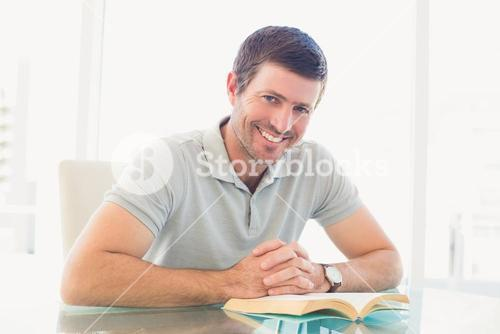 Casual businessman sitting at desk reading a book