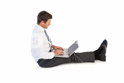 Businessman sitting on the floor typing on his laptop