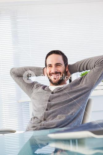Relaxed casual businessman leaning back at his desk