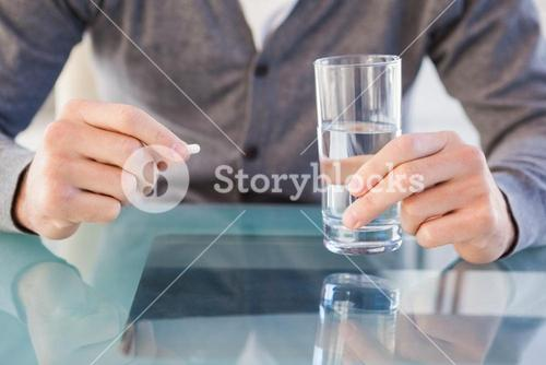 Close up of casual man holding a pill and glass of water