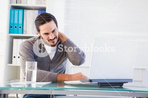 Frowning handsome businessman having neck pain