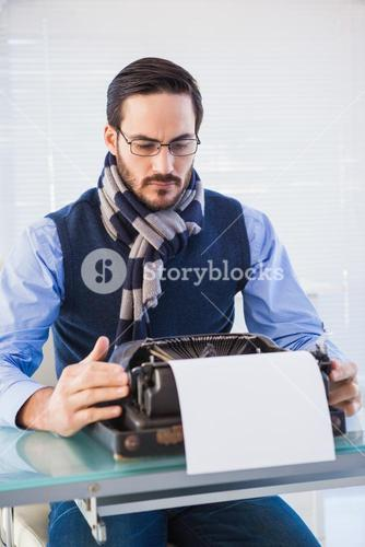 Serious businessman working on typewriter