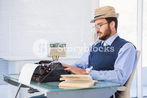Businessman working on typewriter while smoking