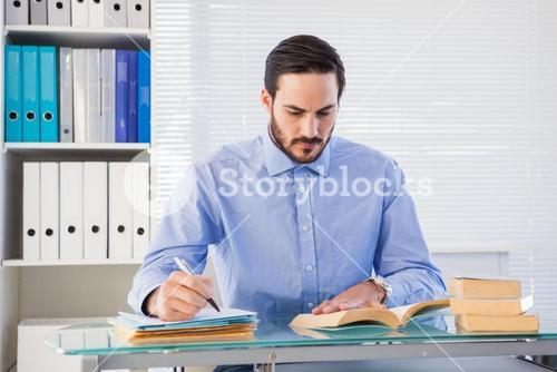 Businessman reading book while writing at his desk