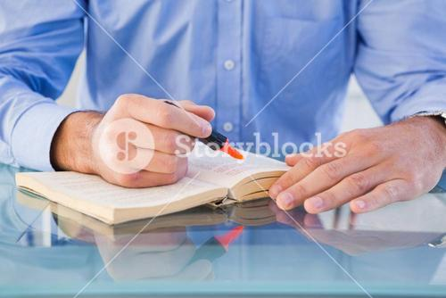 Hands highlighting text in book