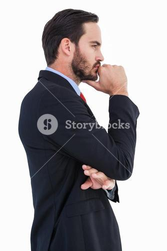 Thinking businessman standing with hand on chin