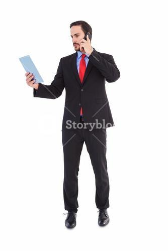 Businessman talking on phone holding tablet pc
