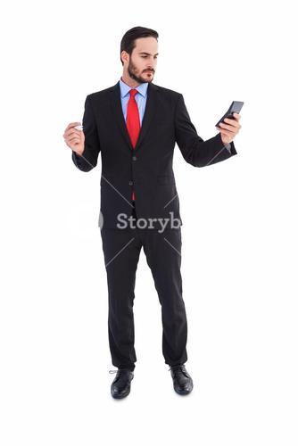 Handsome businessman texting on phone