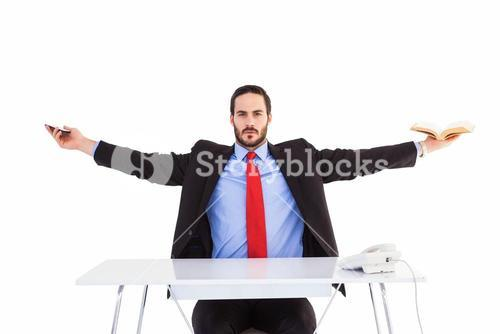 Unsmiling businessman sitting with arms outstretched