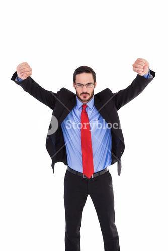 Unsmiling businessman standing with arms raised